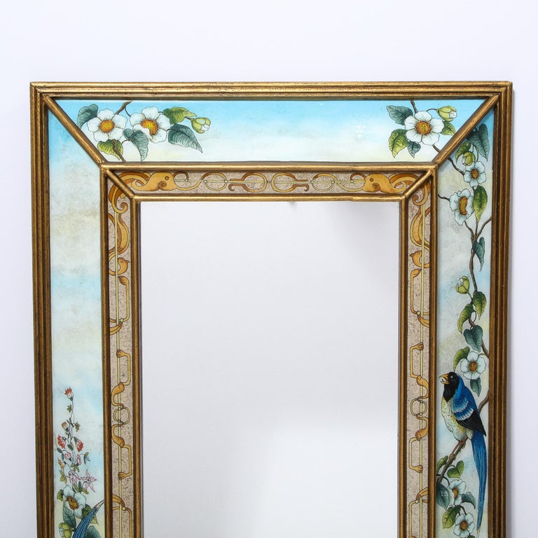 This whimsical and sophisticated Mid-Century Modern mirror was realized in the United States circa 1950. It features a giltwood border with reverse eglomise painted panels depicting a variety of stylized flora and fauna- including apple blossoms and