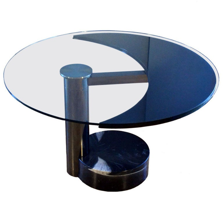 Sculptural dining table revolves in two positions from oval to round. This most exciting table is made with high quality materials and engineering, avantgarde design typical from the 1980's. When the black lacquered moon shape part of the table top