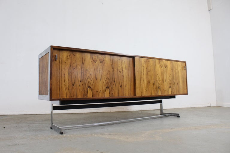 Offered is a beautiful Mid-Century Modern credenza, designed by Richard Young for Merrow Associates. It has chrome legs and pulls. Features two sliding doors with glass shelving on both sides. It is made of full grain wood. It's in very good