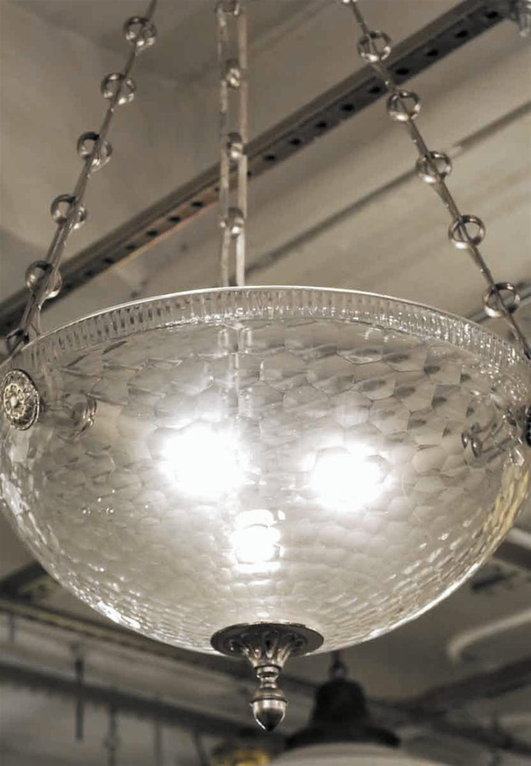 Mid-Century Modern style clear glass bowl pendant light with brushed nickel finished details and a unique chain. This can be seen at our 2420 Broadway location on the upper west side in Manhattan.