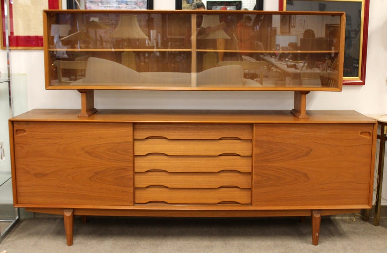 For your consideration is a stupendous and rare, teak credenza, with sliding doors, and a hutch with glass doors, by Rosengren Hansen for Dyrlund, made in Denmark, circa 1960s. In excellent vintage condition. The dimensions are 86.5