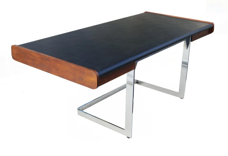 Mid-Century Modern rosewood and chrome desk by Ste. Marie & Laurent. New faux leather vinyl top. The leg opening area is 24.75