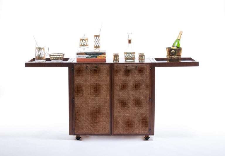 Classic Mid-Century Modern design by Jack Cartwright for Founders featuring a rosewood case, cane-front doors, and brass hardware. This piece was sourced from its original one-owner home and has not moved since new. We styled this bar cart to help