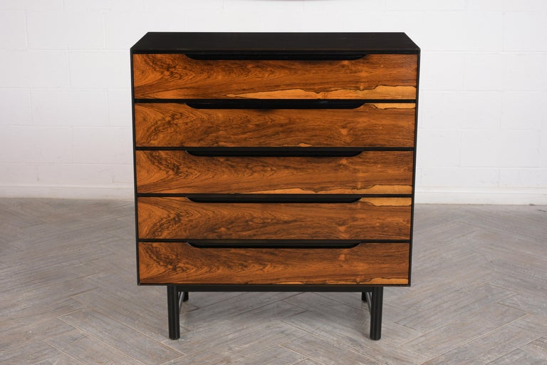 This modern bachelor dresser, circa 1960 is made out of rosewood and has been completely restored. This dresser has dark walnut finish along the top and sides while the drawers show off the natural rich rosewood color. The five drawers have a clear