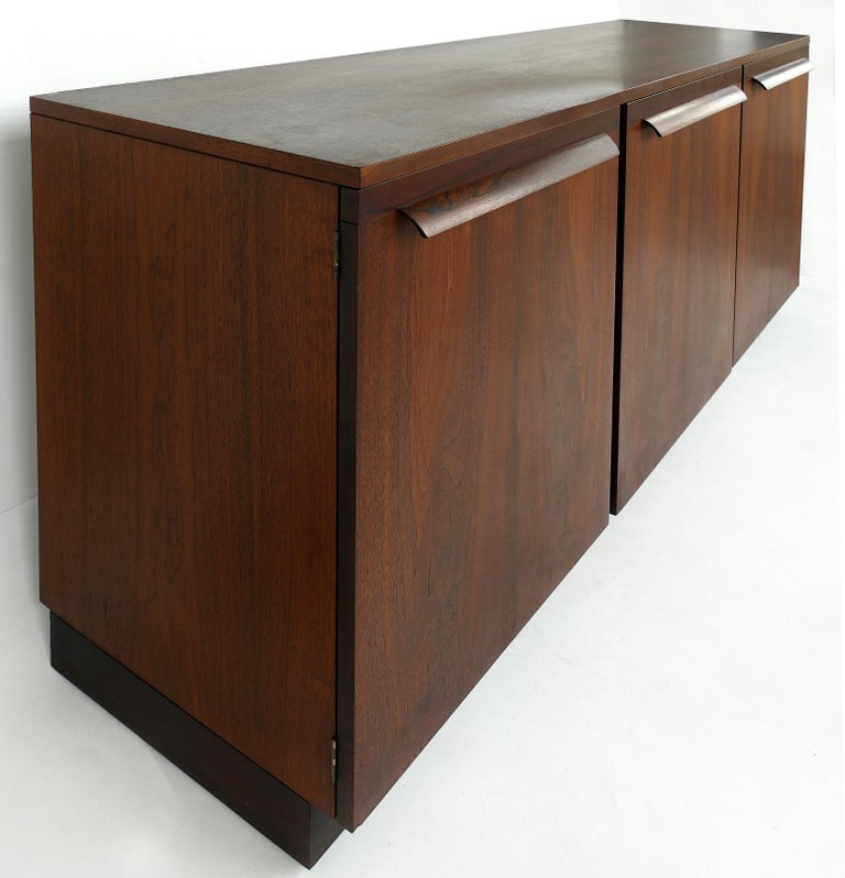 Mid-Century Modern Rosewood Credenza  Offered for is a Mid-Century Modern rosewood credenza with beautifully grained finishes. Two lateral doors open to reveal open shelves. The center door opens to reveal drawers. Each door has a sculptural pull