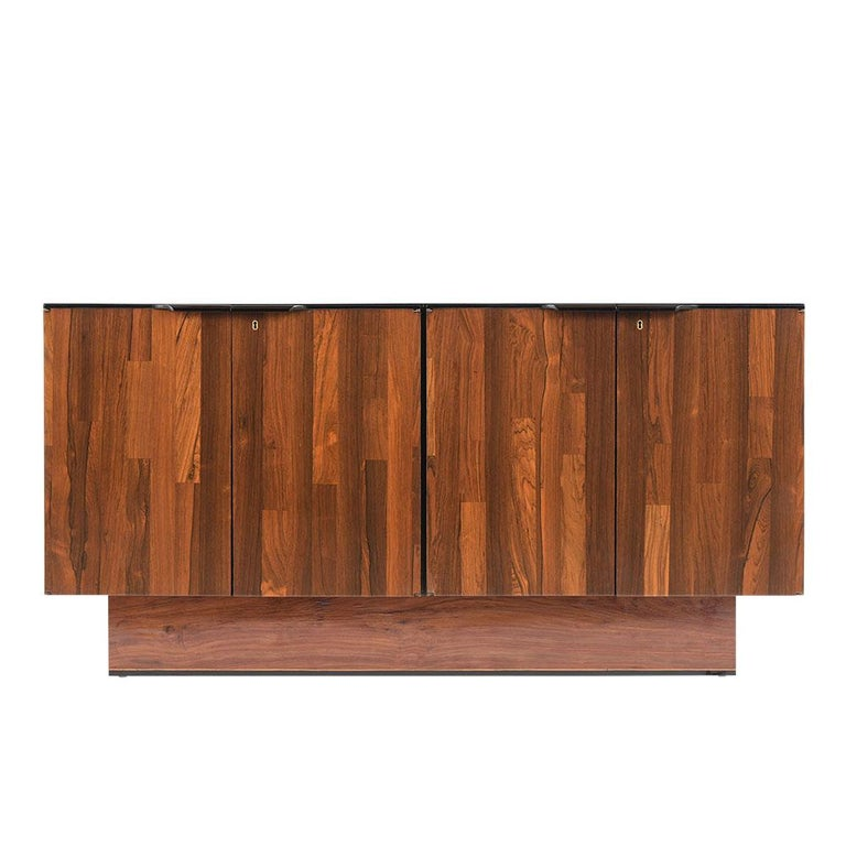 This Mid Century Brazilian Credenza by Barzhay has been fully restored, is made out of rosewood, and finished in a rich dark mahogany & black color combination with a newly lacquered finish. The sideboard comes with four doors with large carved-wood