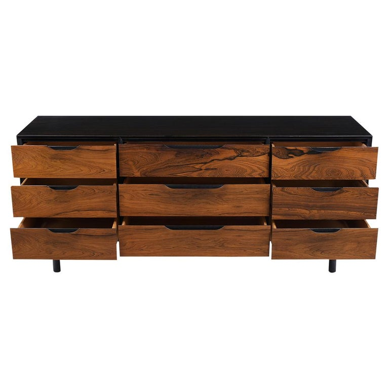 This Mid-Century Modern Dresser has been completed restored is made out of rosewood and newly stained ebonized and rosewood color combination with a lacquer finish. This credenza features an exceptional rosewood grain design, nine drawers that have