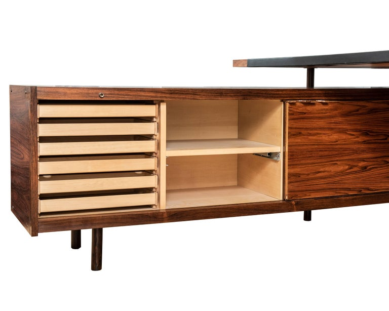 This sumptuous large executive desk in rosewood has a floating leather top, Lucite details, beautiful rosewood grain, and a credenza extension which can be used as a separate sideboard. It is expertly designed to be easily taken apart to facilitate