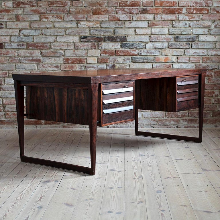 This stunning vintage rosewood desk is a fantastic example of Kai Kristiansen style, one of the most-appreciated Danish designers of 20th century. Pure in form yet very effective. The desk features two spacious dual-sided storage sections. On one