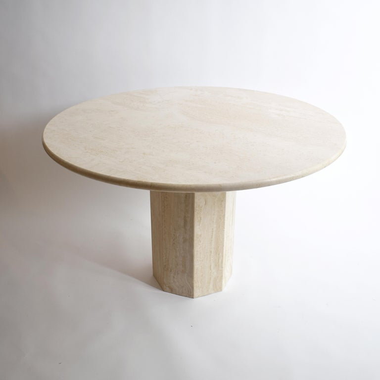 Italian Mid-Century Modern dining table.  Made in cream travertine, with a nice shape and round edge, the top is sitting on a pedestal center foot. Beautiful stone patterns, with sandy effects. This table seats six guests comfortably.