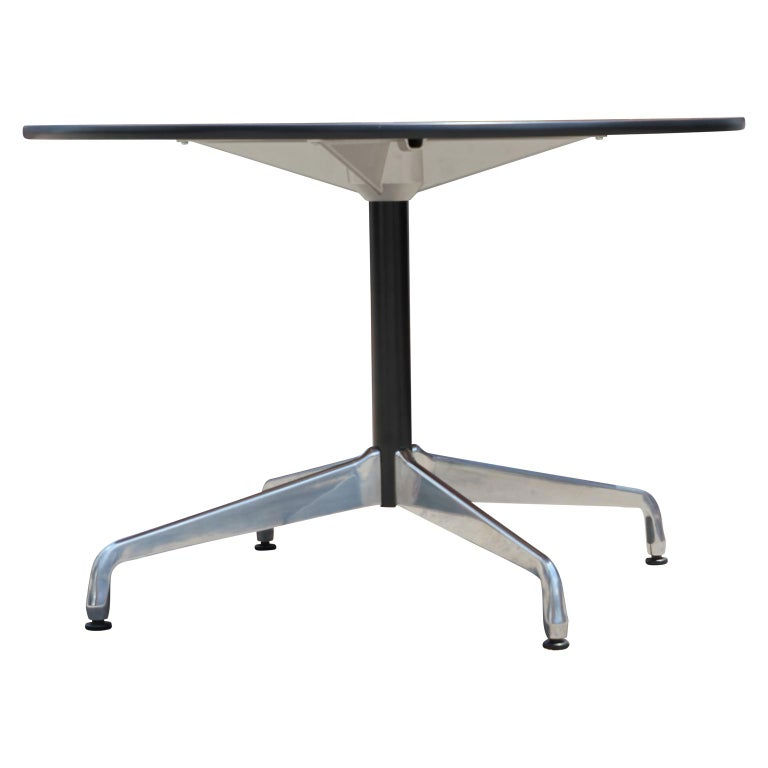 Mid-Century Modern round office table or dining table with a durable chrome base designed by Eames. The table has a dark wood top.