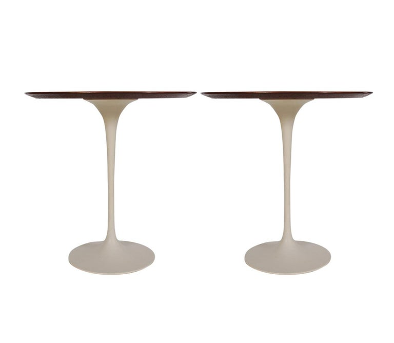 A matching pair of tulip tables designed by Eero Saarinen and produced by Knoll in 1971. These feature gorgeous walnut tops and white tulip bases. Manufacture labels.