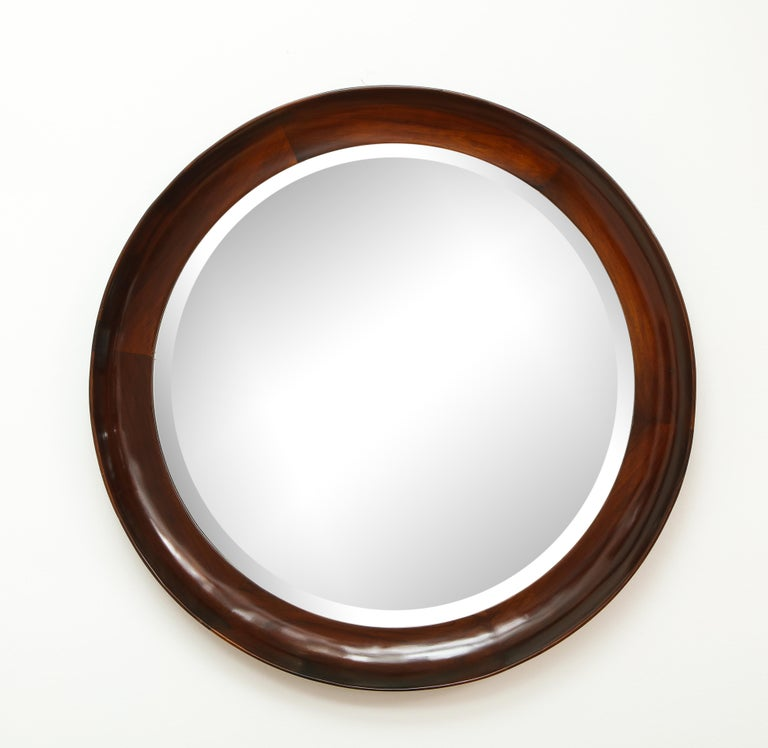 Mid-Century Modern round wall mirror in solid wood frame by Oca Manufacturer, Brazil, 1960s  This vintage wall mirror was manufactured circa 1960s in Brazil. It features an elegant round frame in solid wood, finished in natural varnish maintaining