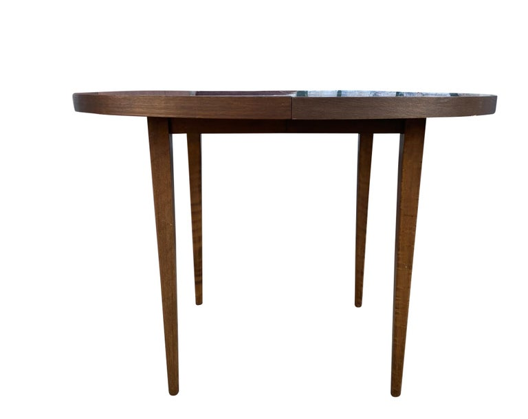 A Mid-Century Modern round walnut extension dining table designed by Paul McCobb for Planner Group Furniture. The table features solid maple with a walnut stain with 4 solid maple lets. The table is in great original vintage condition. Great design.
