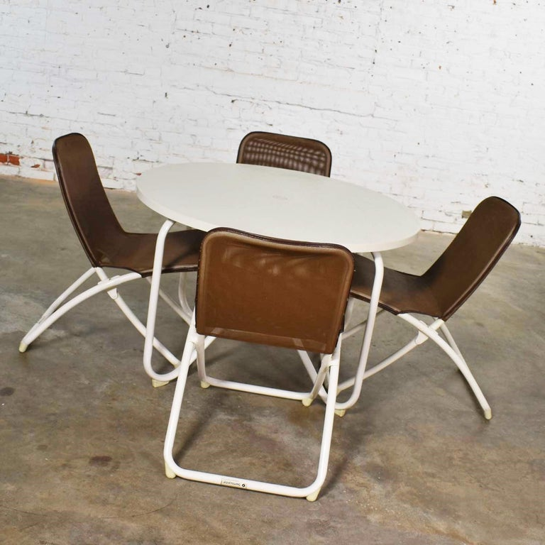 Handsome Mid-Century Modern round patio dining table and 4 folding sling chairs by Samsonite. They are in fabulous vintage condition with no outstanding flaws we have detected. Please see photos, circa 1960s-1970s.  We are in love with this