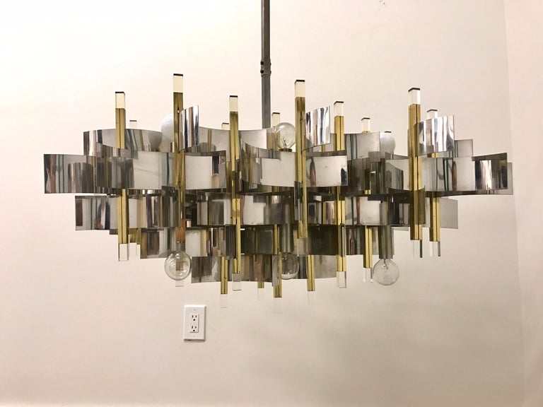 This truly exceptional and iconic chandelier was realized by the esteemed Italian midcentury lighting atelier, Sciolari, circa 1970. It features a wealth of curvilinear nickel bands that connect to polished brass rectangular rods capped with Lucite