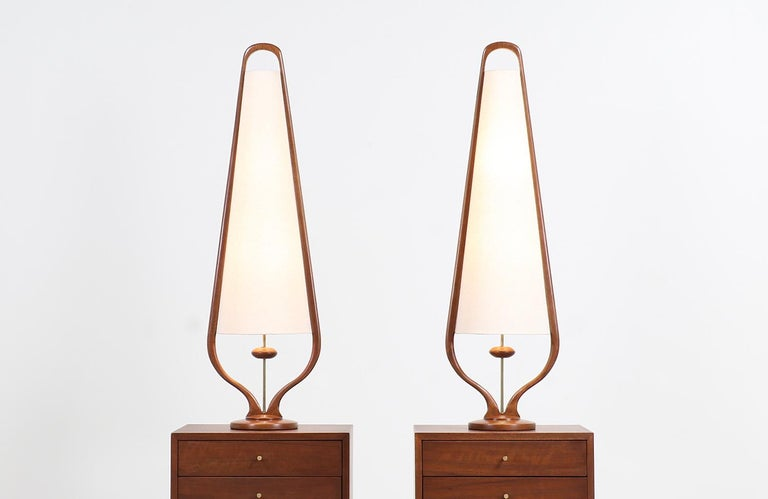 A stylish pair of modern table lamps designed and manufactured by Modeline of California in the United States, circa 1960s. These tall table lamps feature a rounded walnut wood base with a sculpted frame that embraces the new linen shade and