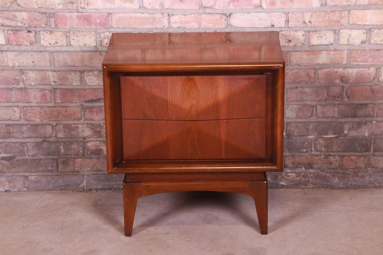 A stunning Mid-Century Modern sculpted walnut diamond front nightstand.  In the manner of Vladimir Kagan  By United Furniture Co.  USA, 1960s  Measures: 23