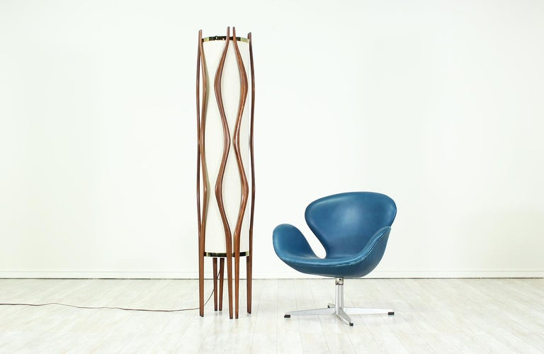 Tall mid-century modern floor lamp designed and manufactured by Modeline Lamp Co. in California circa 1960's. This spectacular design features a sculpted walnut wood body with squiggly paired prongs. The cylindrical linen shade is supported by two