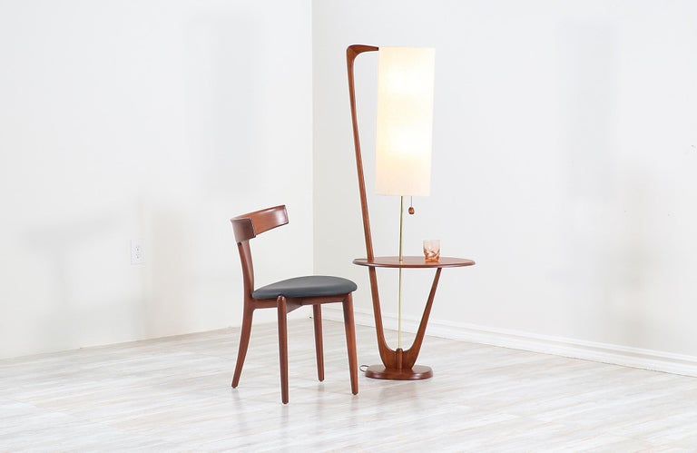 Vintage modern floor lamp designed and manufactured in the United States, circa 1960s. This stylish Mid-Century Modern lamp features a tall and solid walnut wood frame with organic shapes and a stunning grain detail throughout adding a warm flair to