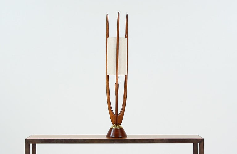 Modern table lamp designed and manufactured by Modeline of California in the United States, circa 1960s. This beautiful and sculptural table lamp features a rounded walnut wood base with elegant polished brass details. The three walnut arms holding