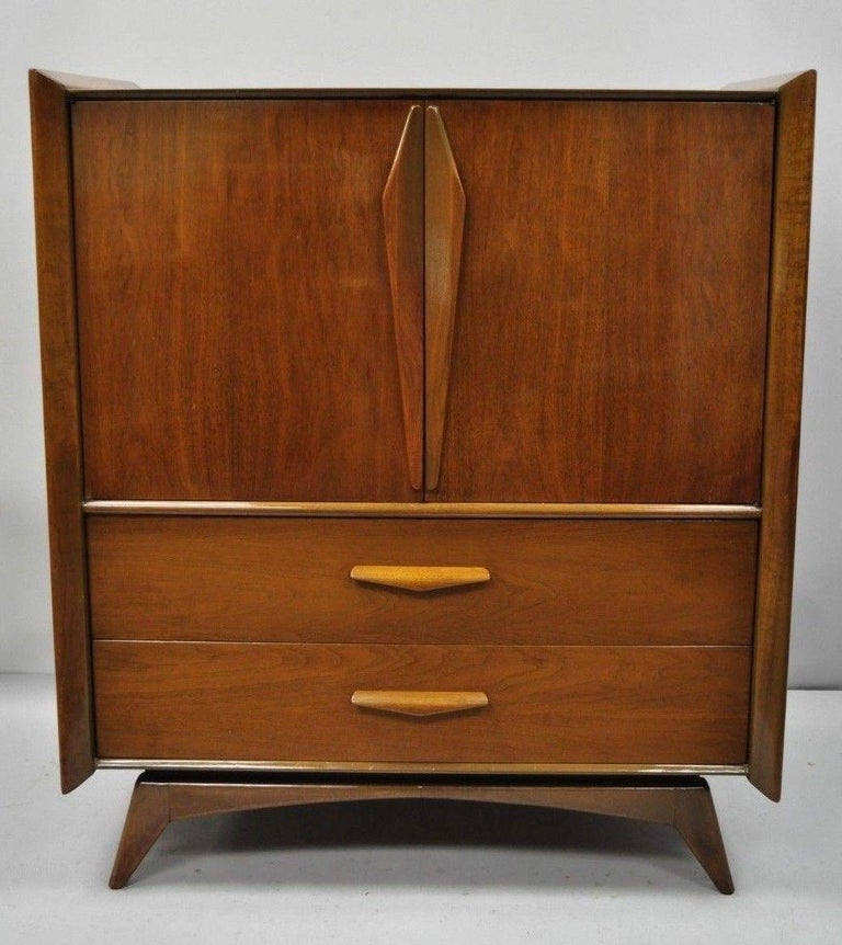 Mid-Century Modern sculpted walnut tall chest dresser. Item features raised panel sculpted wood sides, sculpted wood pulls, angled and tapered legs, two cabinet doors, beautiful wood grain, 5 drawers, sleek sculptural form. circa mid-20th century.