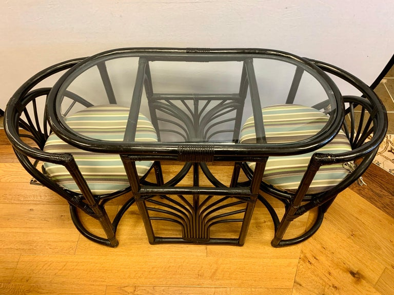 Rare three piece Paul Frankl style oval bistro set. Includes an oval rattan/bamboo table with glass top and two curved chairs that nest inside and then pull out. There is a separate seat cushion on each chair. The set was hand painted black back in