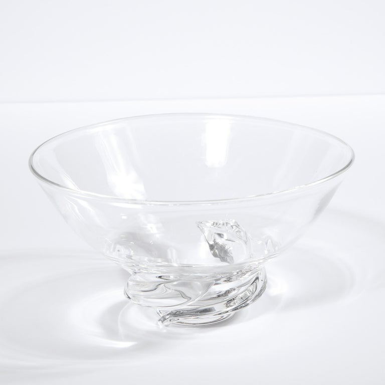 This refined Mid-Century Modern bowl was realized in the United States by the esteemed maker Steuben circa 1960. It features a sculptural swirling base and a subtly flared circular mouth in translucent glass. While this is a perfectly functional