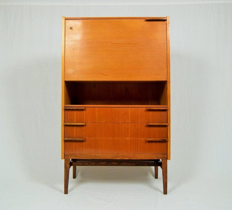 Iconic Secretaire was designed by František Mezulánik for UP Závody in circa 1963. Secretaire features one shelve, three large drawers and hinged door with inner shelves and one little drawer. The hinged door can be used as a writing area desk.