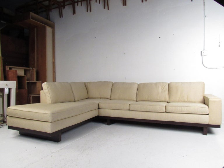 This stunning vintage modern two-piece sofa features eleven overstuffed removable cushions covered in a plush cream colored upholstery. An extremely comfortable sectional with a sturdy sled leg base. The soft decorative fabric and dark toned wood