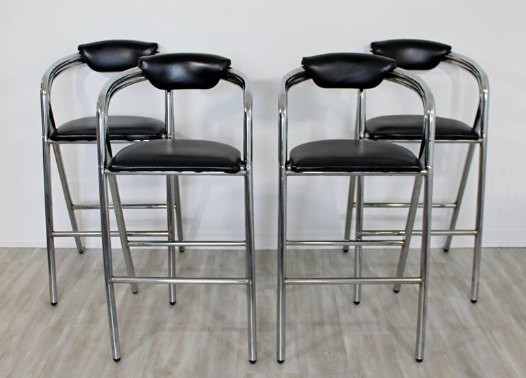 For your consideration is a Classic set of four, tall bar stools, with black leather seats on chrome bases, circa 1970s. In very good vintage condition. The dimensions are 22