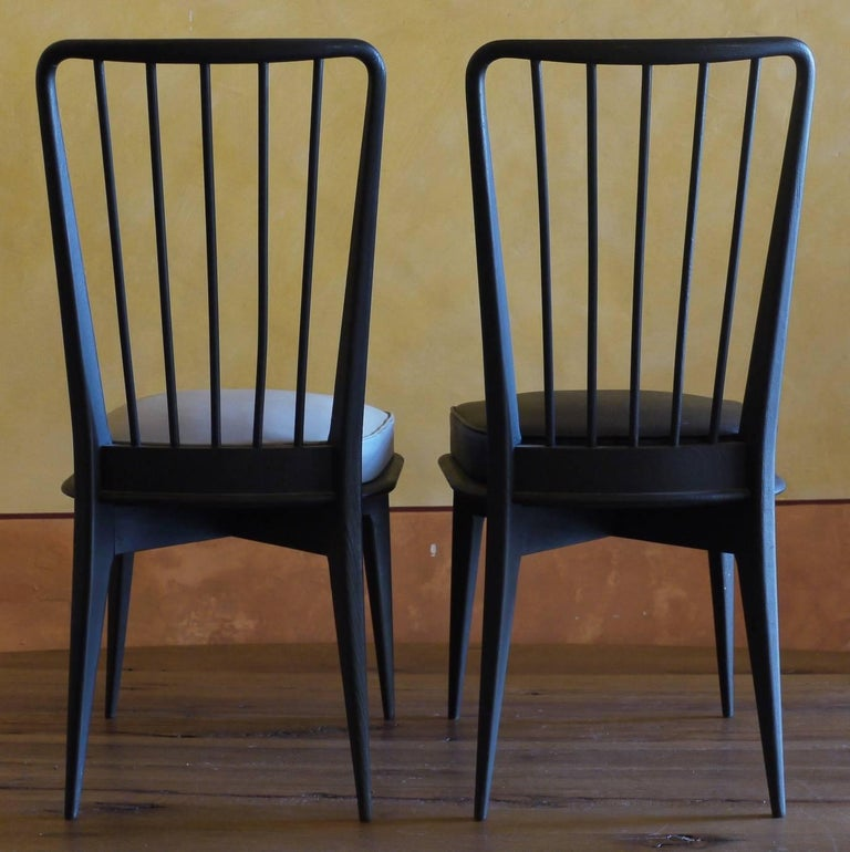 Lot of 6 wood chairs: four with the original grey leatherette sky seats and two recently reupholstered in black leatherette. Size: 42 x 40 x 46 / 90 H. cm.