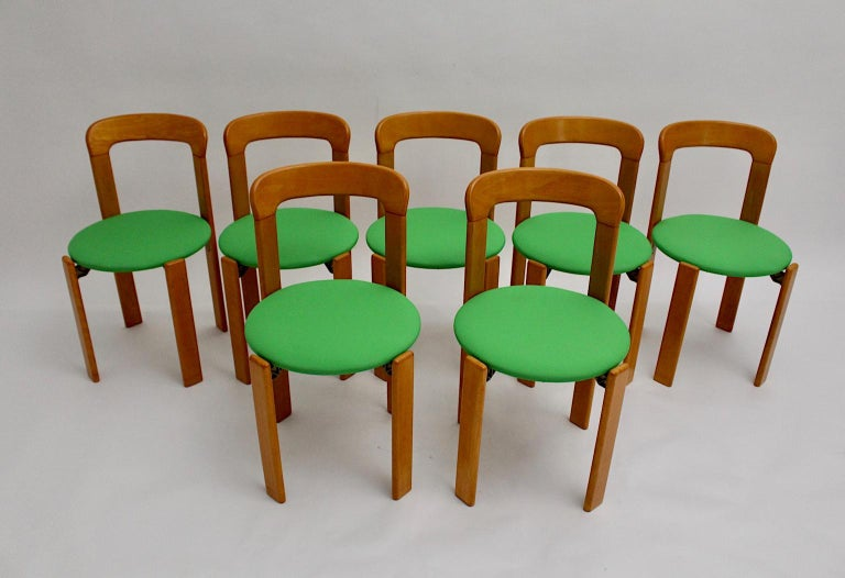 The set of seven dining room chairs were designed by Bruno Rey 1970s Switzerland and executed by Dietiker. The dining room chairs were made of solid beech, laminated plywood beech and cast aluminum. Furthermore the stackable dining room chairs by