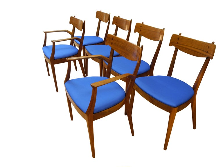 This set of six dining room chairs were designed by Kipp Stewart in the 1950s. The walnut frames have subtle curves and details. There are two armchairs and four side chairs. Sold as a set of six.