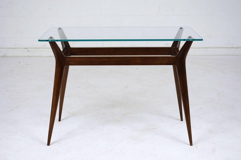 This 1960s Mid-Century Modern-style side table features a teak wood base stained in a rich walnut color with a lacquered finish. The table has a glass top with a flat polish attached to the stretched tapered legs. This side table is sturdy, sleek,