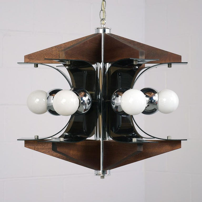 This 1960s Mid-Century Modern chandelier is made of wood with smoked plastic and chrome accents. The top and bottom of the chandelier is finished in a walnut color stained wood. Connecting the wood pieces are curved plastic arcs with the six
