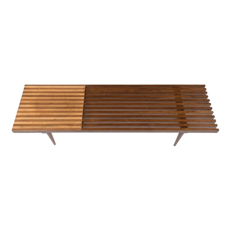 This Mid-Century Modern slatted bench has been recently restored and has its natural wood color with a beautiful polished finish. The bench is made out of walnut, and maple wood combination with a solid wood seat on the side and design. The bench