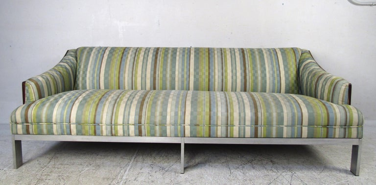 This stunning vintage modern sofa boasts a rich rosewood back and sculpted sides. Six flat bar chrome legs and overstuffed seating show quality construction and ensure maximum comfort. A colorful vintage fabric adds to the midcentury appeal. This
