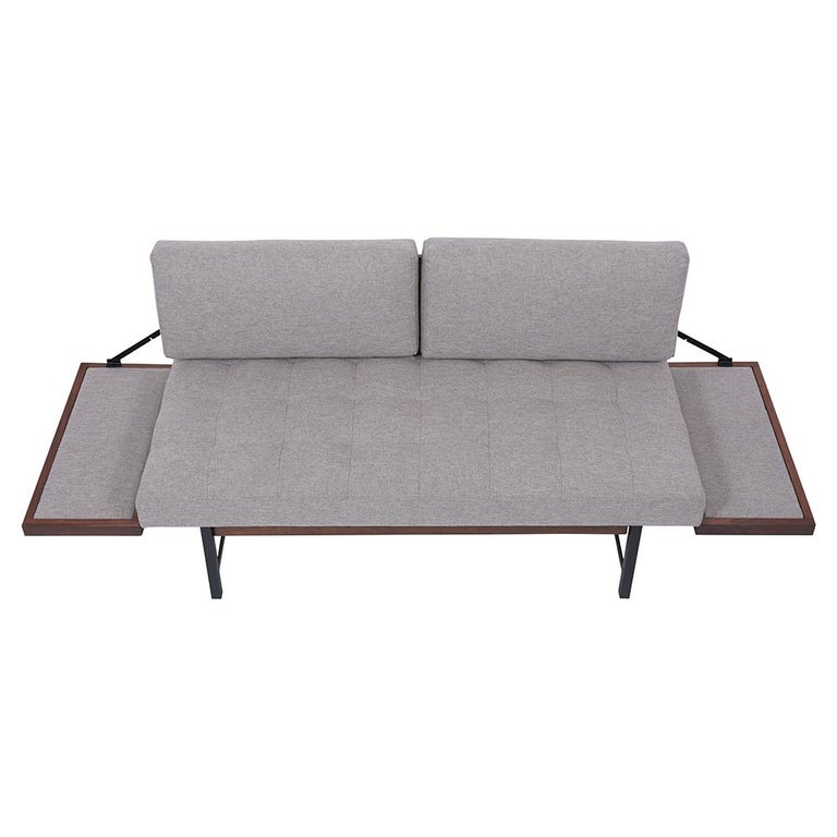 This Mid-Century Sofa Bed is crafted out of walnut wood and metal combination that has been fully restored. This sofa features a squared tufted design seat, two backrest cushions, and is newly upholstered in a grey fabric with new foam inserts. The
