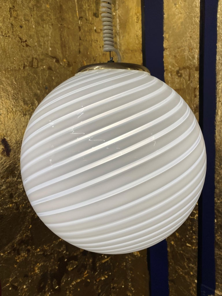 Space Age pendant light manufactured in white and clear striped hand blown Murano glass, attributed to Venini, circa 1970. Measures: Diameter is 33cm. Height is 60cm but can be easily adjusted to measure. The coiled cable is original to the lamp