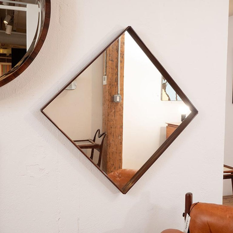 Mid-Century Modern square wall mirror nested in a delicate solid wood frame, Brazil 1960s  This graceful vintage wall mirror was manufactured circa 1960s in Brazil. It features a delicate solid wood frame with rounded-edges and beveled corners,