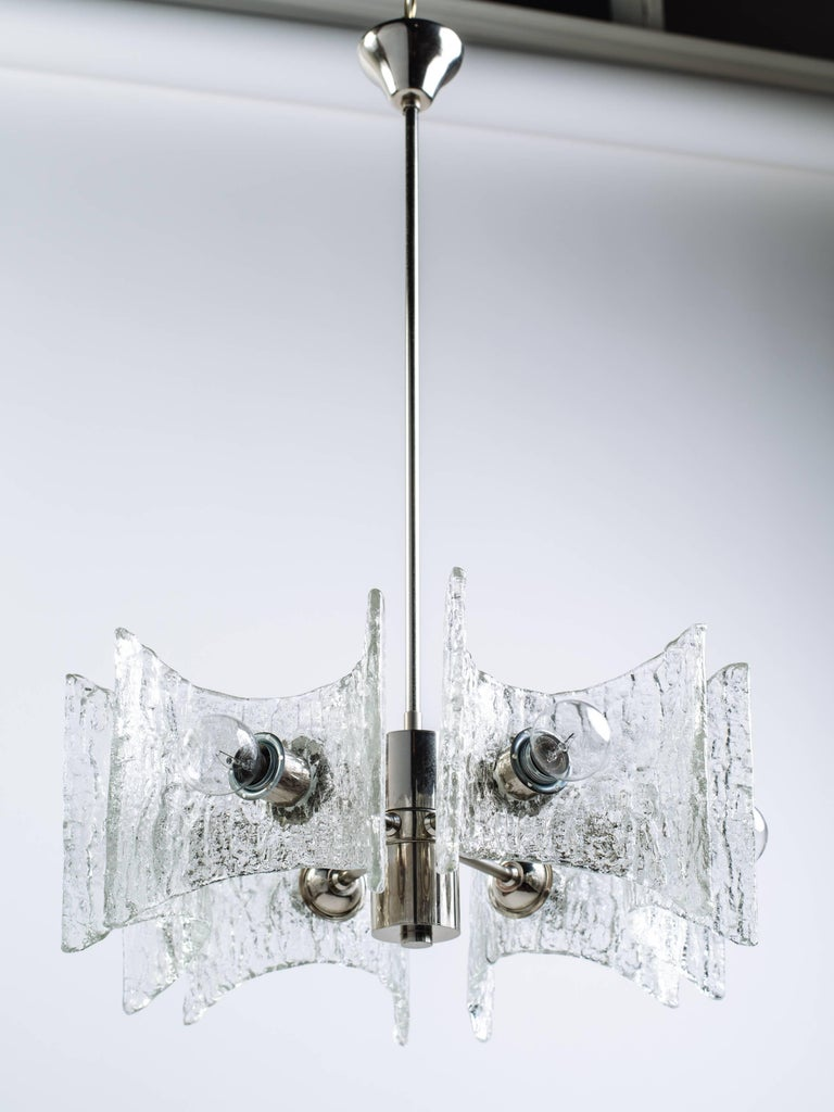 German Mid-Century Modern starburst pendant chandelier with brilliant textured glass and chrome metal frame. The chandelier is fitted with six lights and hand blown shades featuring curvature design with stylized pointed corners. Designed by Kalmar,