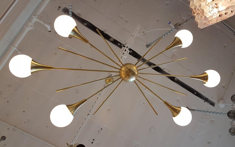 Mid-Century Modern Italian, Stilnovo style, six-arm brass and six white glass globes, Sputnik chandelier. Made of a brass centre ball, with six brass tubes at the same height on each side. Beautiful patina on the brass. The height is adjustable