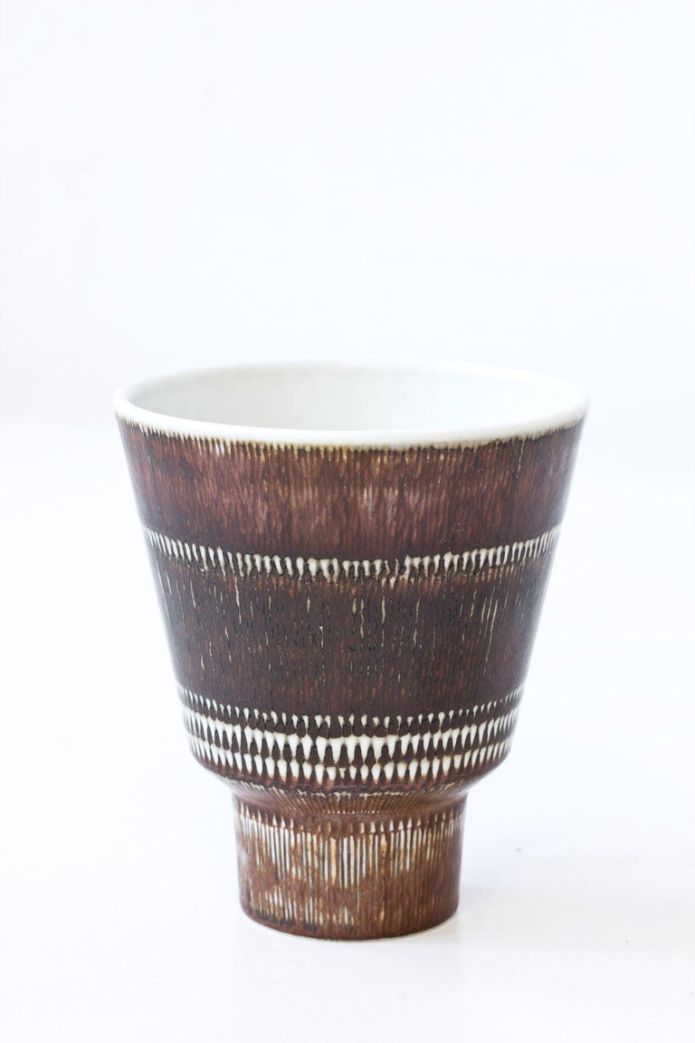 Vintage ceramic vase designed by Hertha Bengtsson for Rörstrand.  Handmade in Sweden during the 1950s.  Made from stoneware with an incised brown glaze. White inside.  Signed on the bottom.