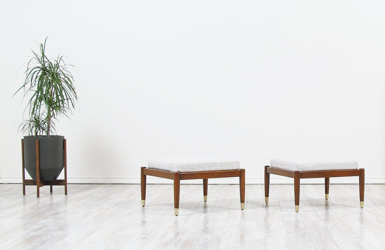 A pair of elegant modern stools designed by Folke Ohlsson for DUX of Sweden in Sweden circa 1950s. This stylish pair of stools are made of solid walnut wood with brass sabots in all four legs. Both stools have been refinished and reupholstered by