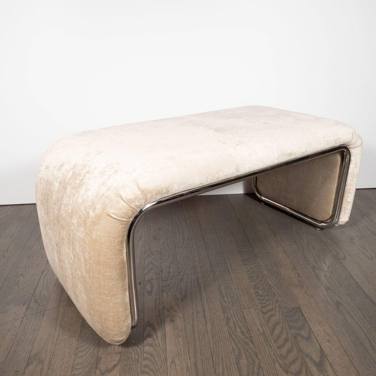 This refined bench was realized in the United States, circa 1970. Representative of the American Art Deco movement, it features streamlined sides- an iconic deco design element- that gently curve at each end. The exposed chrome traces this form