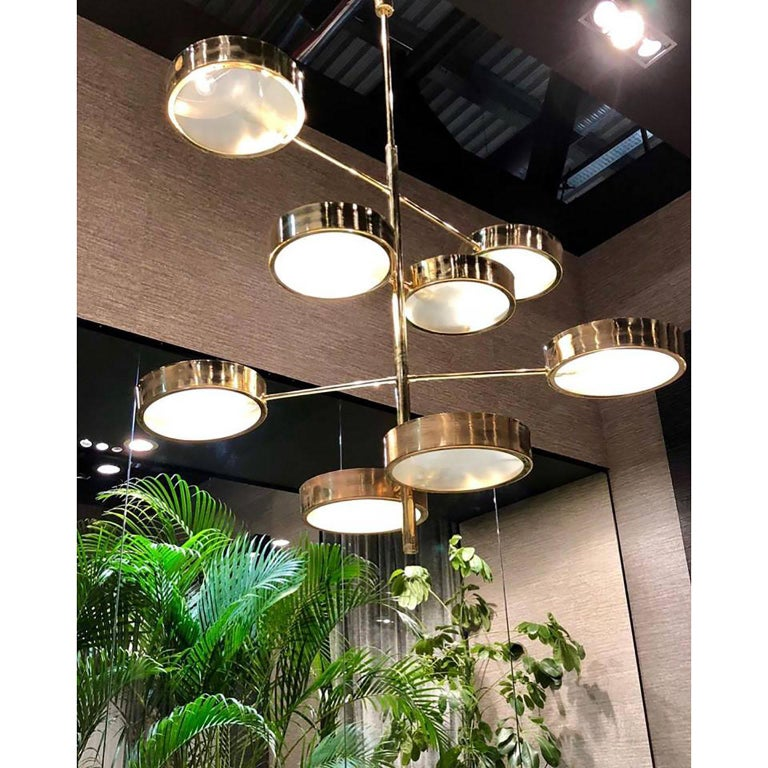 Important architectural ceiling lamp with eight lights. Four adjustable arms made of brass, ending each side with a brass and glass shade. Dimensions: Slightly customizable both on vertical and horizontal Height 130 cm (51.18 inches), diameter