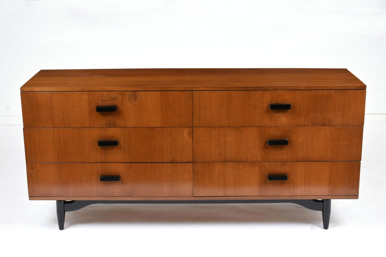 This 1960s Mid-Century Modern style chest of drawers is stained in a light walnut color and black color with a lacquered finish. This chest featured six drawers with ample storage space and carved wood handles finished in black color. The Chest is