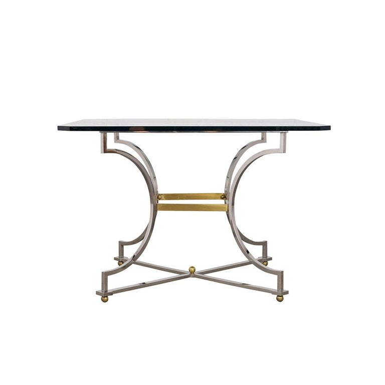 This Mid-Century Modern dining table features a chrome pedestal base with brass accents. The tabletop is made of 3/8? thick clear beveled glass and is in excellent condition with no scratches. This dining table is sturdy, sleek, and ready to be used