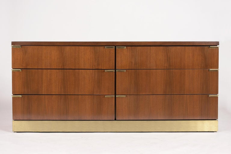 This Mid Century style Credenza by Glenn of California has been professionally restored and newly stained in a dark walnut color with a semi-gloss lacquered finish. The credenza has six large drawers each with two brass pull handles on each side,